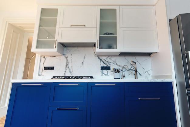 モダンなキッチンのすっきりとしたインテリアデザイン。大理石のタイル張りのバックスプラッシュを備えたキッチンの豪華な青と白の家具。シンク、調理台、シンプルな食器棚を備えたモダンな新しいキッチン。