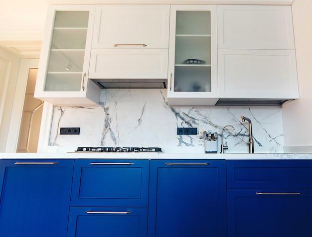 モダンなキッチンのすっきりとしたインテリアデザイン。大理石のタイル張りのバックスプラッシュを備えたキッチンの豪華な青と白の家具。