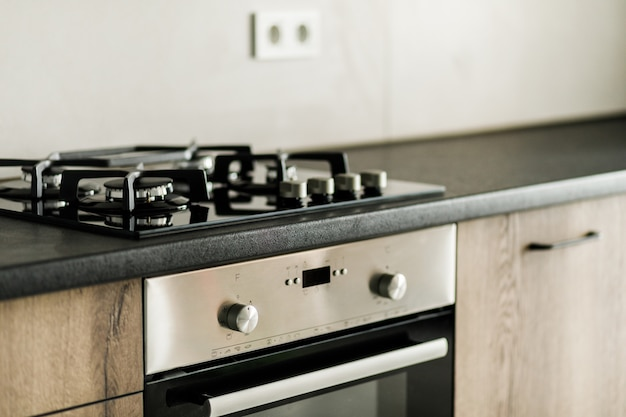 Modern kitchen, close up, gas stove with cooking pan, white and gray minimalistic interior design.