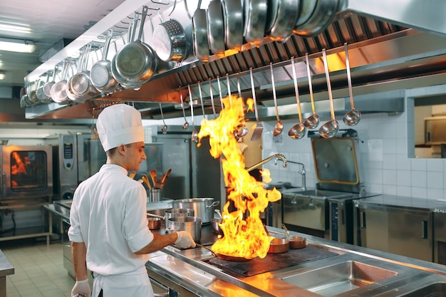 Современная кухня. повара готовят еду на плите на кухне ресторана или гостиницы. пожар на кухне.