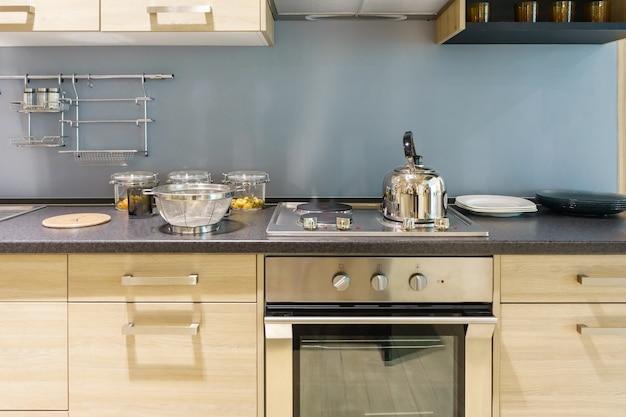 Современная кухонная мебель с современной посудой, как капот, индукция и духовка
