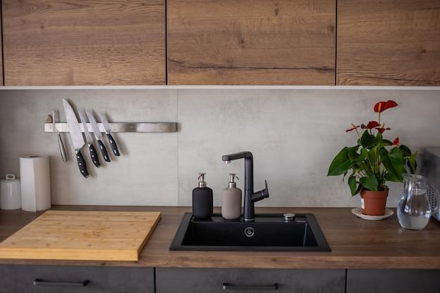 Современная кухня в серых тонах и деревянные шкафы дома с посудой