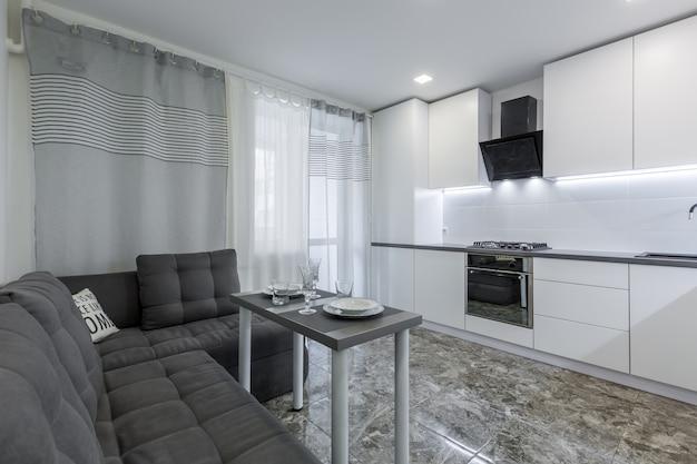 Современная кухня в светлых белых тонах с черной мраморной плиткой на полу в небольшой квартире