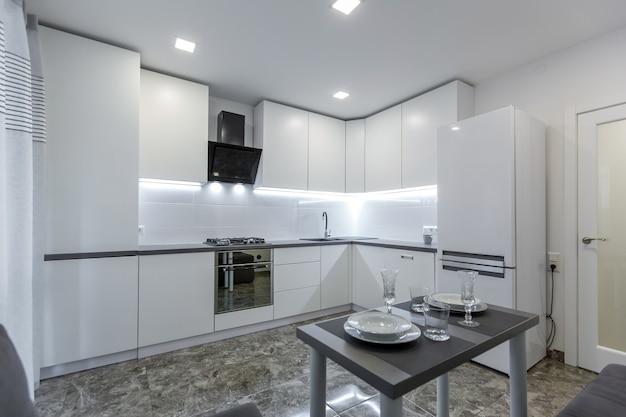 작은 아파트에 배치 된 바닥에 검은 대리석 타일이있는 밝은 흰색 톤의 현대적인 주방
