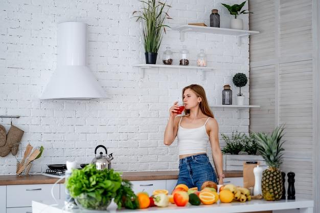 Интерьер современной кухни. концепция диеты. портрет здоровой молодой женщины с красивой фигурой возле стола с фруктами и овощами на кухне, концепция здорового питания.