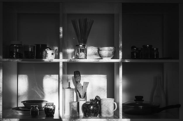 Интерьер современной кухни. минималистичный стиль дома. кухонная утварь и посуда на белых полках.