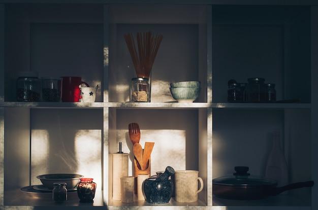 Интерьер современной кухни. откройте шкаф с чистой посудой. открытые полки на кухне. хорошо организованная концепция кухни. минималистичный стиль дома. кухонная утварь и посуда на белых полках.