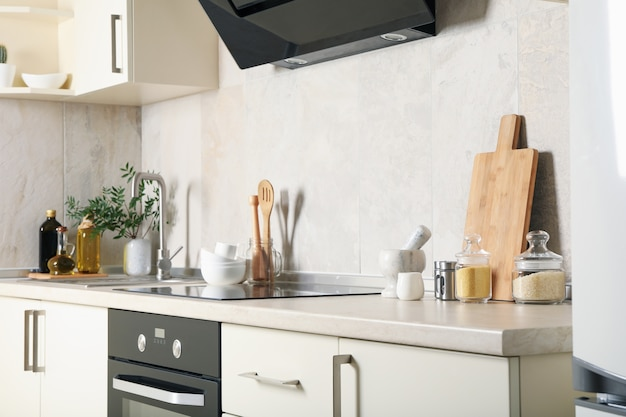 Modern kitchen interior with different supplies in light colors
