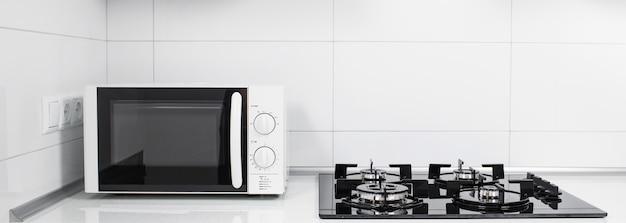 Современный интерьер кухни с электрической плитой и микроволновой печью
