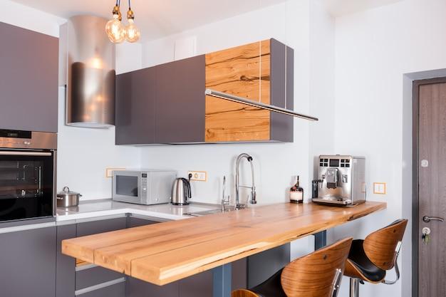Современный интерьер кухни с огнями на коричневый деревянный стол и барные стулья, кофемашина.