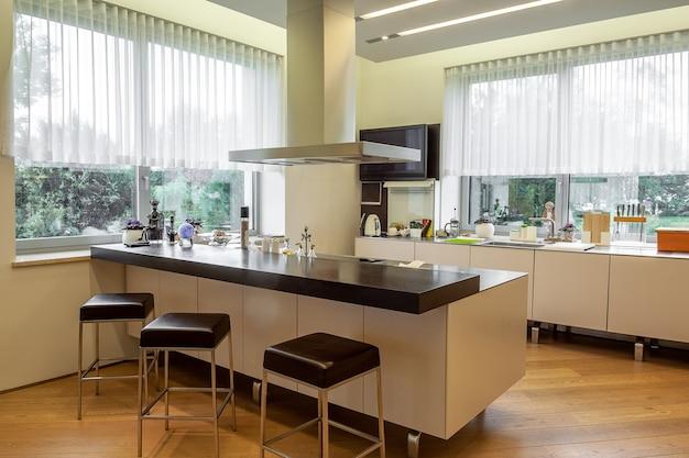 広い窓の機能的な家具や電化製品を備えたモダンなキッチンインテリア