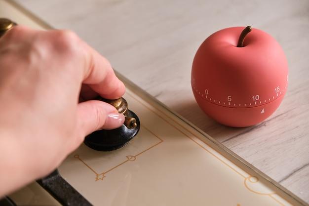 キッチンのコンロの近くに形作られたモダンなキッチンタイマーアップル