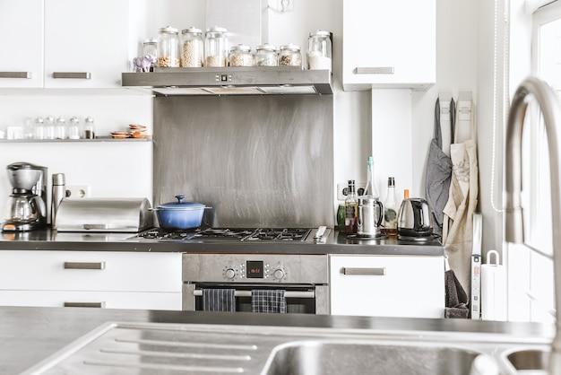 흰색 캐비닛과 스테인레스 추출기 후드 및 일광에서 오븐이있는 검은 색 카운터가있는 현대적인 주방