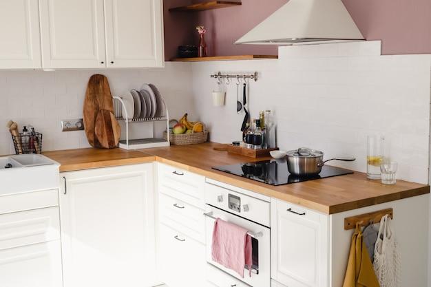 Современная кухня с белыми шкафами, деревянной стойкой и обеденным столом в солнечном свете в дневное время. полный комплект кухонного оборудования.