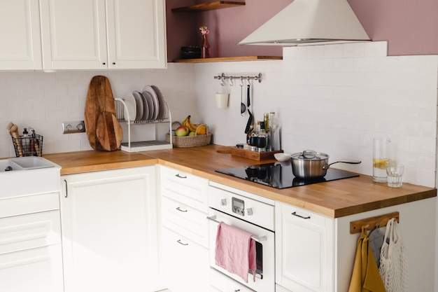 Modern kitchen with white cabinets, wood counter and dining table in sunlight in daytime. full set of kitchen equipment.