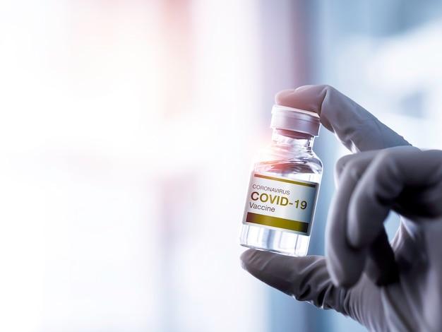 コピースペースのある実験室で手袋を着用している科学者の手によって示されているボトルバイアル上の現代のラベルcovid19ワクチン