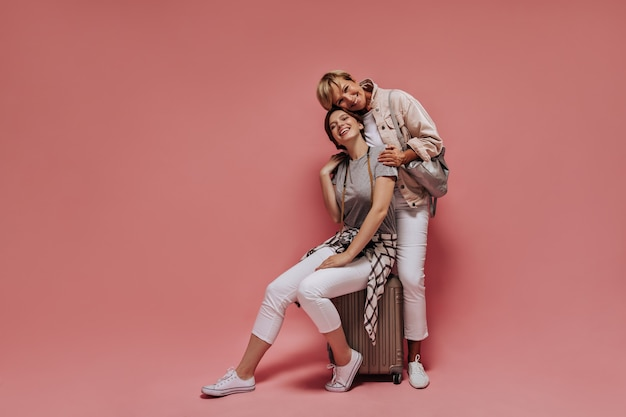 Modern lady with brunette hair in plaid shirt and white pants sitting on suitcase and posing with smiling woman in light outfit on pink backdrop.