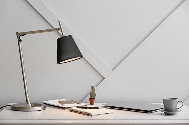 部屋のテーブルに置かれたモダンなランプと文房具