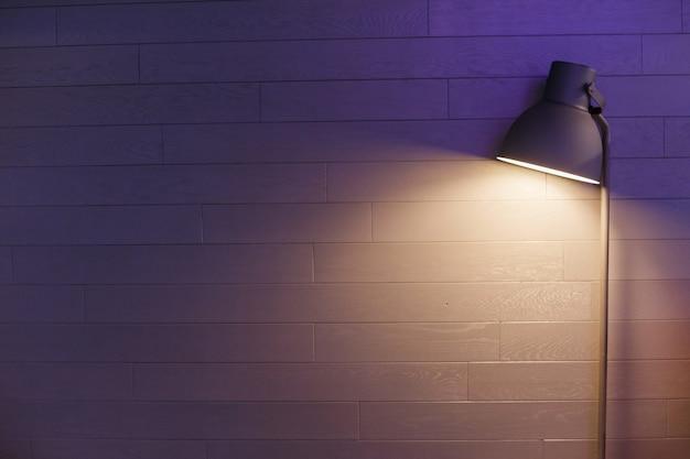 파란색 벽에 현대 램프입니다. 어두운 시끄러운 사진.