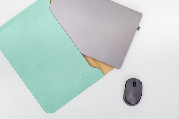 Modern laptop in comfortable case mint colored on white background. closed personal computer pulled out of fashionable bag. workspace concept. top view. flat lay.