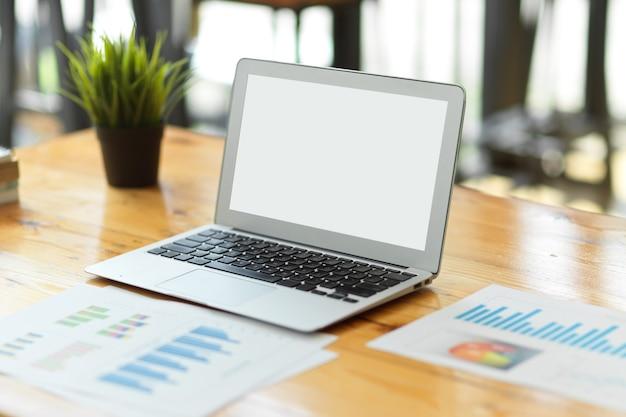 Макет пустого экрана современного ноутбука на деревянном рабочем столе с финансовым отчетом, рабочим местом для бизнеса, столом бухгалтера