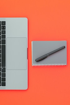 Modern laptop and notepad with a pen isolated on a red surface