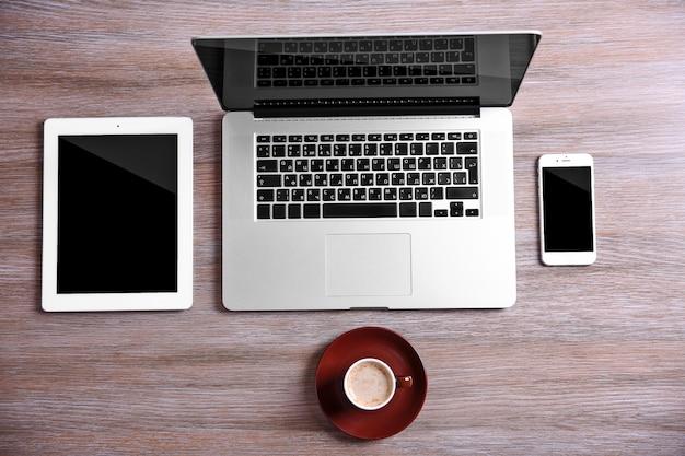 현대 노트북, 스마트 폰 및 태블릿 나무 테이블에 커피 컵