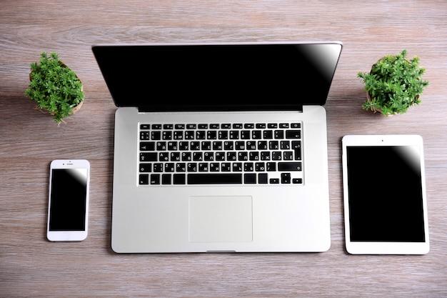 木製のテーブルに小さな緑の植物と現代のラップトップ、スマートフォン、タブレット