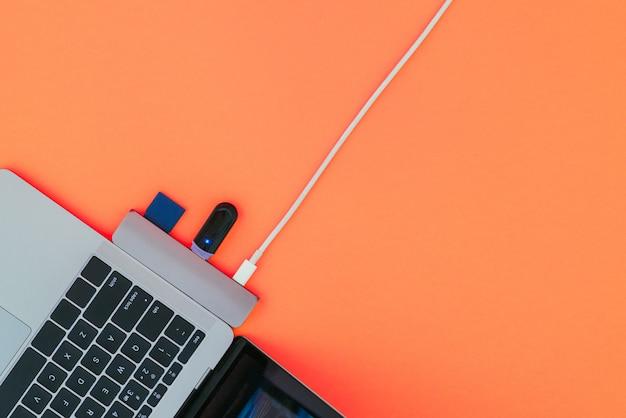 Современный ноутбук, usb-адаптер type-c со вспышкой и зарядкой на красной поверхности