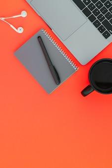 Современный ноутбук, белые наушники, серый блокнот с ручкой и чашка кофе на красной поверхности