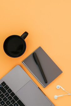 Modern laptop, white headphones, gray notebook with a pen and a cup of coffee on the orange surface