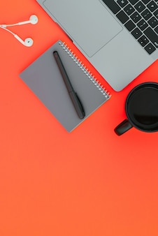 Modern laptop, white headphones, gray notebook with a pen and a cup of coffee on the red surface