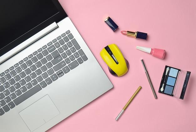 Современный ноутбук, беспроводная мышь, косметика на розовом пастельном фоне, минимализм, вид сверху, плоская планировка