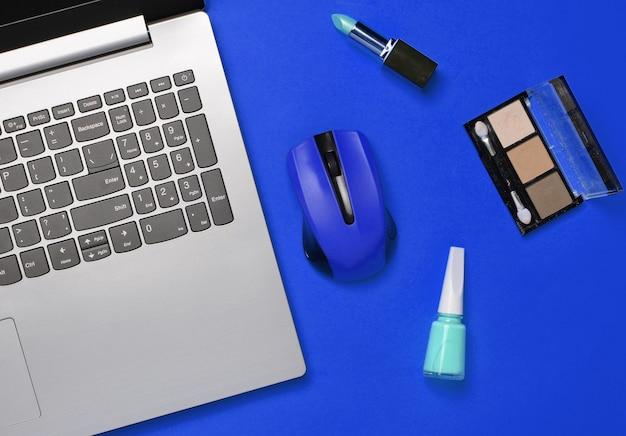 Современный ноутбук, беспроводная мышь, косметика на синем фоне