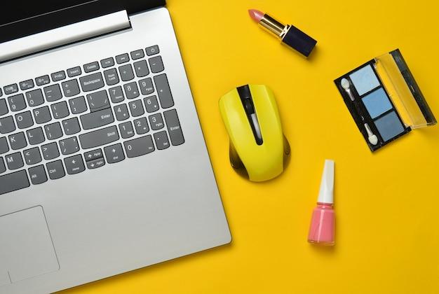 Modern laptop, wireless mouse, cosmetics on a yellow pastel background, minimalism, top view, flat lay