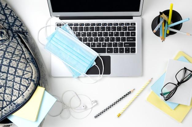 Современный ноутбук с рюкзаком и канцелярских принадлежностей на белом столе