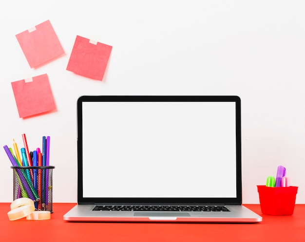 Modern laptop with blank adhesive notes on white wall