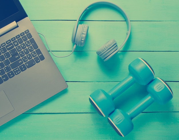 Modern laptop with headphones and dumbells