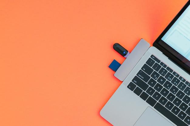 Современный ноутбук с usb-адаптером type-c и флешками изолирован на красной поверхности