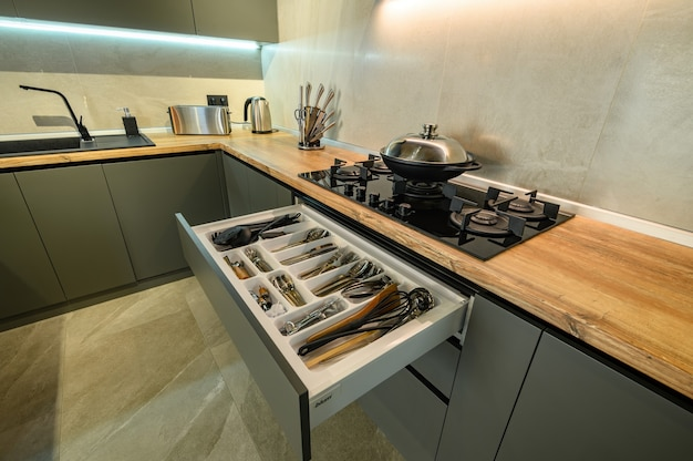 Modern large luxury dark gray kitchen with pulled out drawer