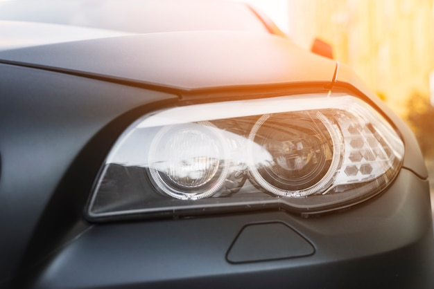 Modern led headlight of dark car on street