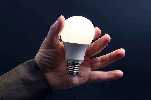 Современная светодиодная лампа получилась. включен светодиодный светильник в ладони человека на темной стене. электротехническая промышленность