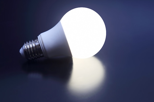 Современная светодиодная лампа включена на темный фон. электротехническая промышленность