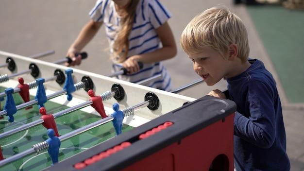 Современная жизнь в большом городе - дети играют в настольный хоккей на улице