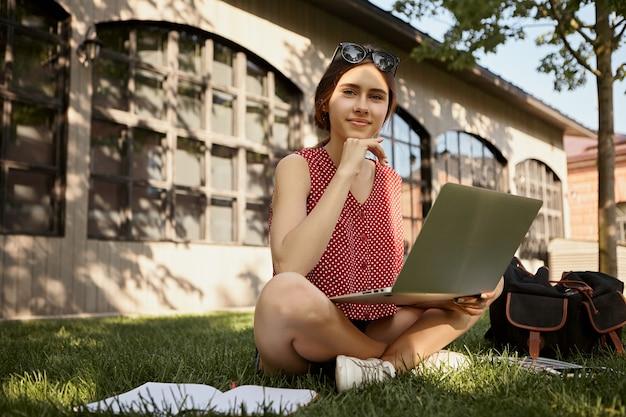 Современный образ жизни, электронные устройства, общение и сети. открытый снимок стильной красивой молодой европейской студентки, сидящей на траве со скрещенными ногами, используя портативный компьютер
