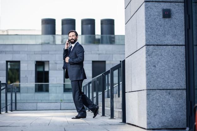 現代のライフスタイル。笑顔で電話で話しているうれしそうな自信を持ってビジネスマン