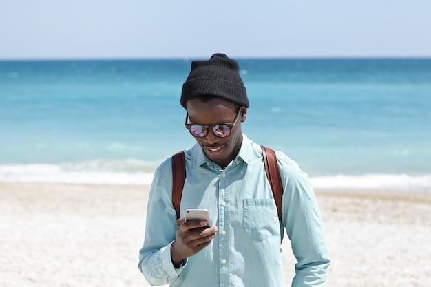 現代のライフスタイル、技術、コミュニケーションの概念。海辺で週末を過ごしながら、高速3gまたは4gインターネットを楽しむシャツ、帽子、サングラスの魅力的な若い黒のヨーロッパのヒップスター