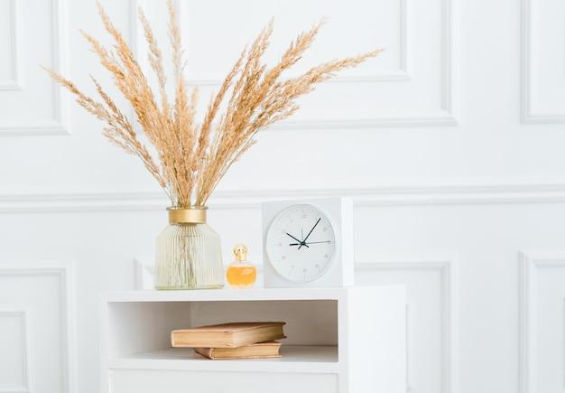 花、時計の本、香水瓶が置かれたヴィンテージのコーヒーテーブルを備えたモダンで明るいインテリア。