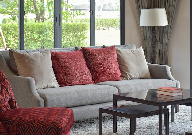 Modern living room design with red pillows on sofa and decorative table lamp