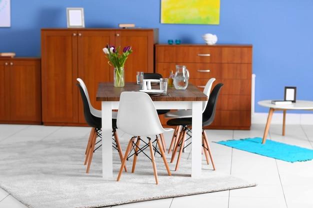 モダンなリビング ルーム。テーブルと椅子を備えた家具セット。テーブルの上の美しい白と紫のチューリップの花束